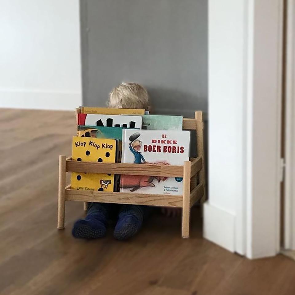 jongetje verstopt zich achter boekenkast
